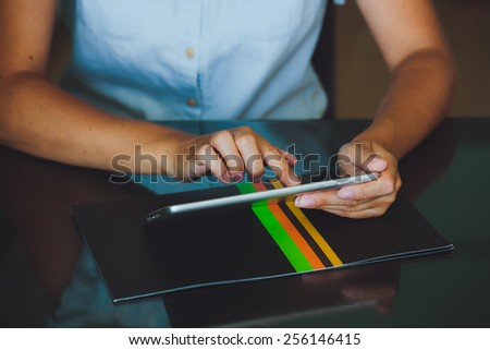 One light-skinned hand belonging to a woman holds a large tablet while the other hand uses a pointer finger to access something on the tablets touch screen display.  - stock photo