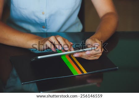 One light-skinned hand belonging to a woman holds a large tablet while the other hand uses a pointer finger to access something he tablet has a gray case and a glass screen.  - stock photo