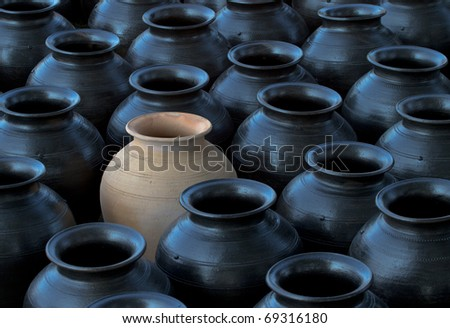 one lighten jar in many black jars. - stock photo