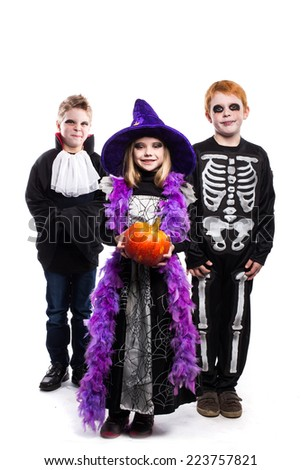 One little girl and two boys dressed the Halloween costumes: witch, skeleton, vampire. Studio portrait isolated over white background - stock photo