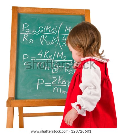 One little girl is looking at physics formulas on the blackboard and thinking. Vertical.