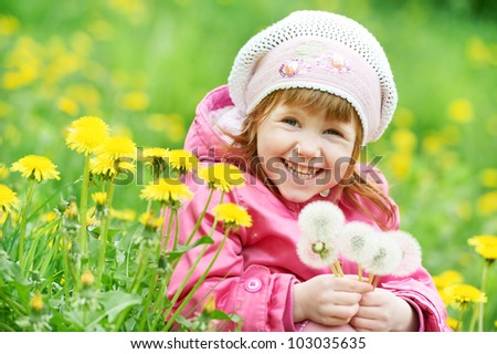 One little happy smiling girl with dandelion on summer or spring flower field - stock photo