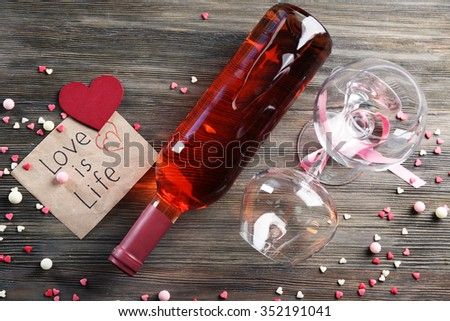 One love, one life concept - wine bottle and glasses with hearts around, close up