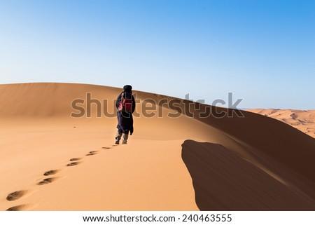 One male tuareg climbing a dune in the desert. - stock photo