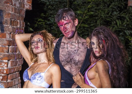 One man and two bloodied girl in lingerie on the background of a brick wall - stock photo
