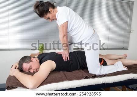 One man and woman performing back shiatsu massage - stock photo