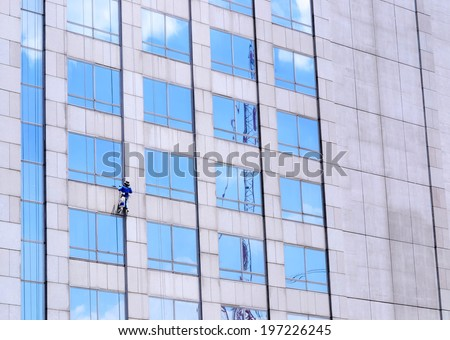 one man cleaning windows on a big building - stock photo