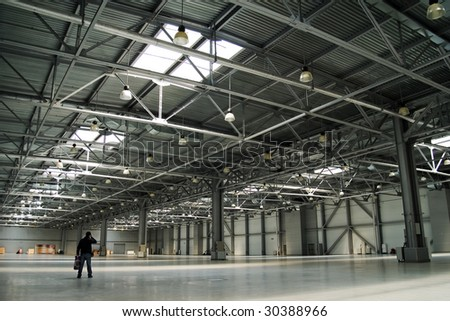 one man in the big empty storehouse - stock photo