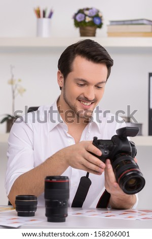 One man in white shirt is looking at photo in camera. Choosing photos