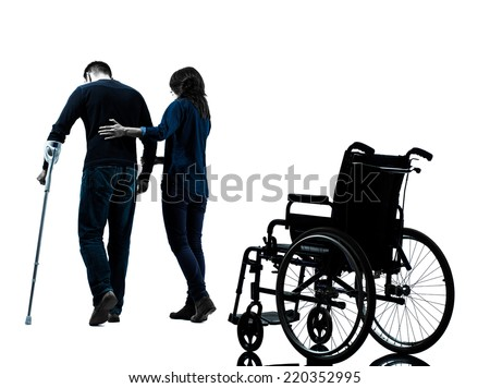 one man injured man with woman walking away from wheelchair with crutches in silhouette studio on white background - stock photo