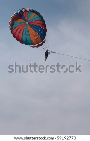 One man is para sailing over the clean sea. - stock photo