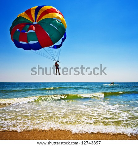One man is parasailing over the blue sea. - stock photo