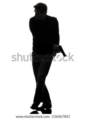 one man killer policeman holding gun walking silhouette studio white background - stock photo