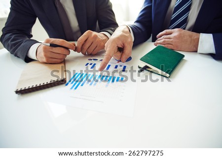 One man pointing to another man at diagram - stock photo
