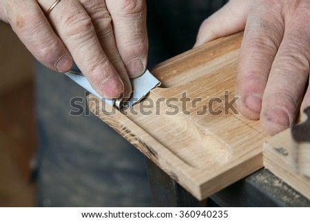 One man sandpaper grinds wood product in a workshop on the table