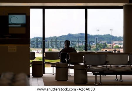 One man sitting in a seat at an airport waiting for a loved one or business client to arrive. - stock photo