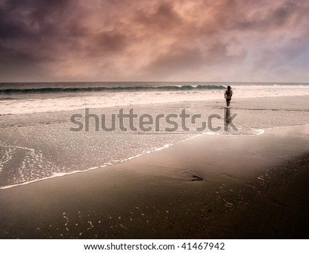 One man walking along the water's edge on a fantasy beach.