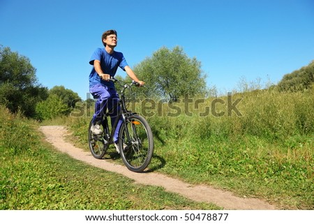 one man wearing sporty clothes is riding on bicycle. sunny summer day. wide angle.