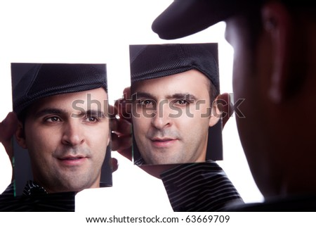 One man, with face on the mirror, isolated on white, studio shot - stock photo