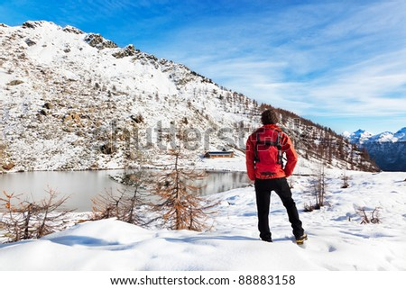 One man young male hiker stands in front of a alpine lake looking to the snowy landscape, rear view. Large copy-space at top-right. Buffet Lake, Champorcher, Val d'aosta, Italy, Europe. - stock photo