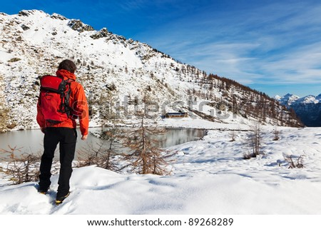 One man young male hiker stands in front of a alpine lake looking to the snowy landscape, rear view. Large copy-space at top-right. Buffet Lake, Champorcher, Val d'aosta, Italy, Europe.