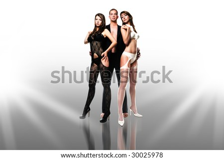 One men with two girl/threesome/Super model group - stock photo