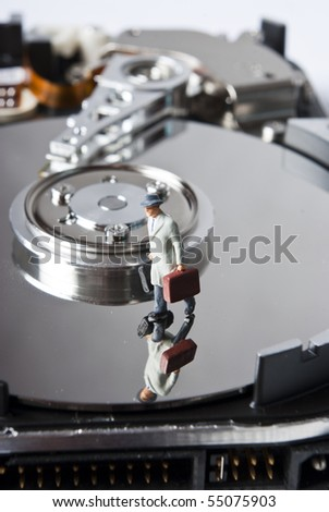 one miniature man with suitcase on hard drive - stock photo
