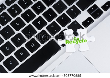 """One missing puzzle with green """"Go Recycle"""" text on laptop keyboard as background, business, finance and online concept - stock photo"""
