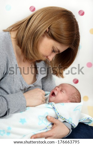 One-month old baby boy crying in his mother's arms.