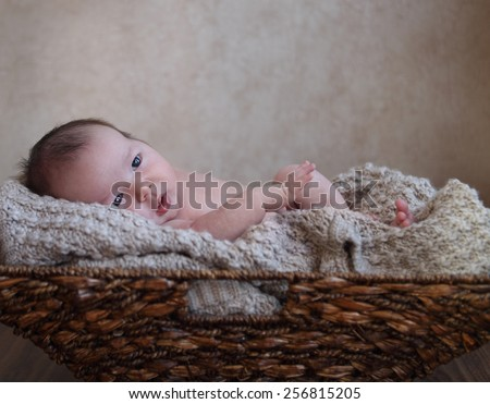 One month old baby boy in the basket on the wooden floor - stock photo