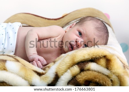 One-month old baby boy lying on a blanket.