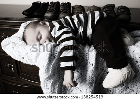 One month old baby boy sleeping in a drawer - stock photo