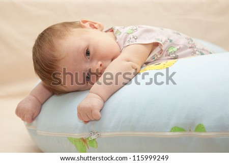 One month old baby lying on his tummy on the blue pillow. Baby looking at the camera. Selective focus on baby face - stock photo