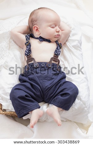 One month old newborn baby boy wearing pants  and suspenders. - stock photo