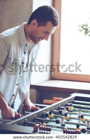 One more goal. Side view of cheerful young handsome man playing foosball game and looking excited while standing in front of window - stock photo