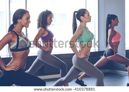 One more time girls! Side view of beautiful young women with perfect bodies in sportswear exercising with smile while standing in front of window at gym  - stock photo