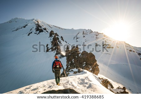 One mountaineer climbs rocky, snowy mountain at dawn. - stock photo