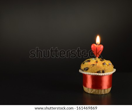 One muffin with burning candle on black background - stock photo