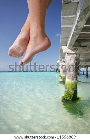 One of a large series. Great set of legs hanging over the edge of a tropical jetty. - stock photo