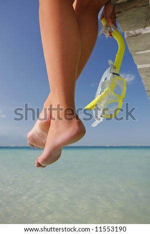 One of a large series. Great set of legs hanging over the edge of a tropical jetty with a diving mask. - stock photo