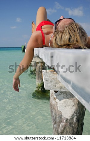 One of a large series. Woman in red bikini sunbathing on a tropical jetty