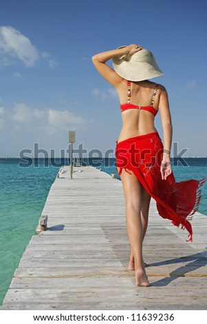 One of a large series. Woman in red bikini walking down a tropical jetty - stock photo