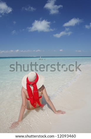 One of a large series. Woman in straw hat sunbathing by the water's edge on a tropical beach. - stock photo