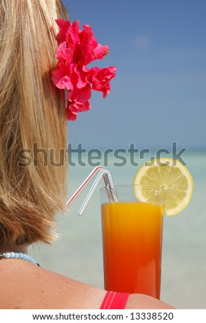 One of a large series. Woman sitting on a beach with a cocktail - stock photo