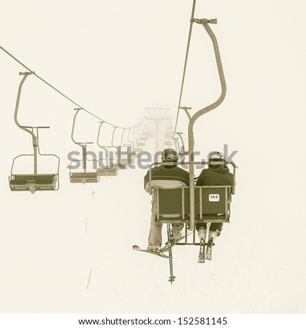 One of chair lifts in a ski resort of a valley of Zillertal in the fog - Mayrhofen region, Austria (stylized retro) - stock photo