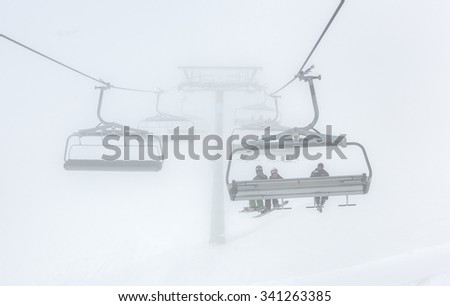 One of chair lifts in a ski resort of a valley of Zillertal in the foggy weather - Mayrhofen region, Austria - stock photo