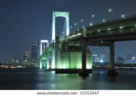 one of famous Tokyo landmarks, Tokyo Rainbow bridge over bay waters with scenic night illumination - stock photo