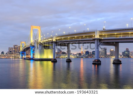 one of famous Tokyo landmarks, Tokyo Rainbow suspension bridge supports over night waters with scenic colourful illumination - stock photo