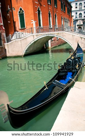 One of famous Venetian gondolas laid up at its moorings against a cityscape with red house and bridge - stock photo
