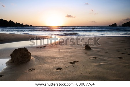 One of Malta's favorite beaches - Ghajn Tuffieha Beach at sunset with a group of unidentifiable young adults playing in the waves. - stock photo